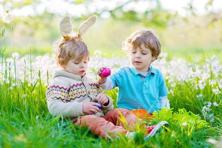 Two little boy friends in Easter bunny ears during egg hunt
