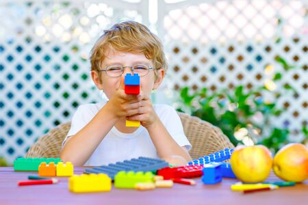 Little kid boy playing with colorful plastic blocks Stock Photo