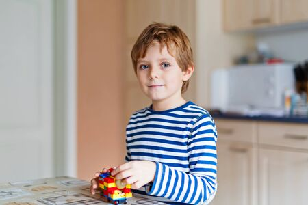 school kid boy playing with lots of small colorful plastic blocks