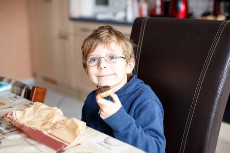 school cafeteria: little school boy eating donut indoor in a canteen.