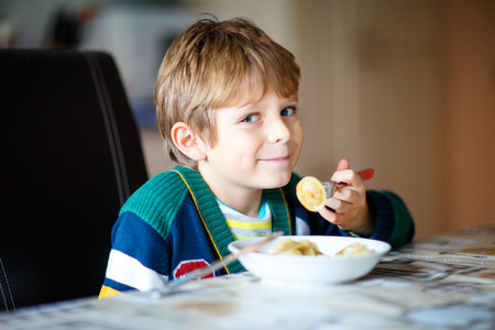 comedor escolar: little school boy eating pasta indoor in a canteen. Foto de archivo