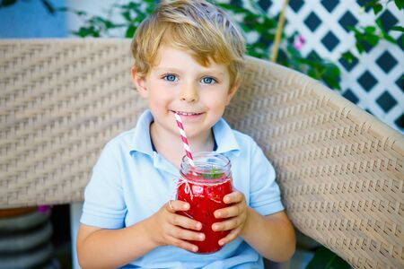 Little Kid boy drinking healthy fruit smoothie