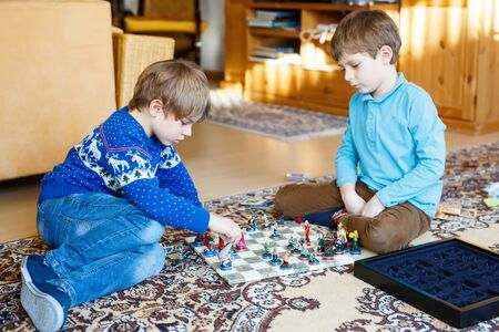 Two little kid boys playing chess game at home. Stock Photo