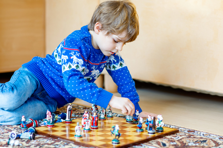 Little preschool kid boy playing chess game at home