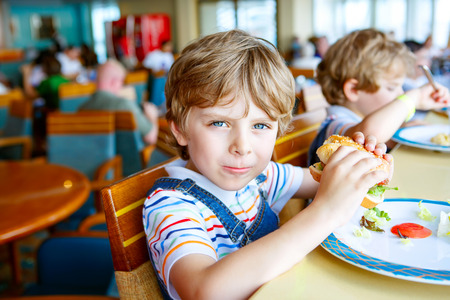 Cute healthy preschool boy eats hamburger sitting in school canteen 스톡 콘텐츠