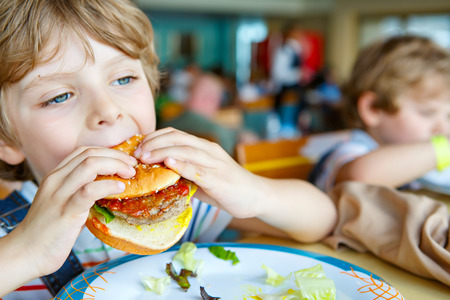 comedor escolar: Cute healthy preschool boy eats hamburger sitting in school canteen Foto de archivo