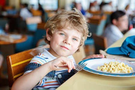 Cute healthy preschool boy eats pasta sitting in school canteen