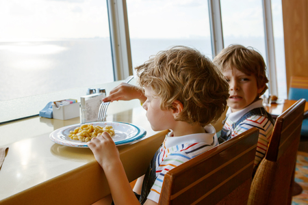 comedor escolar: Two preschool kids boys eats pasta sitting in school canteen Foto de archivo