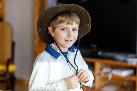 Portrait of little school kid boy wearing cowboy hat