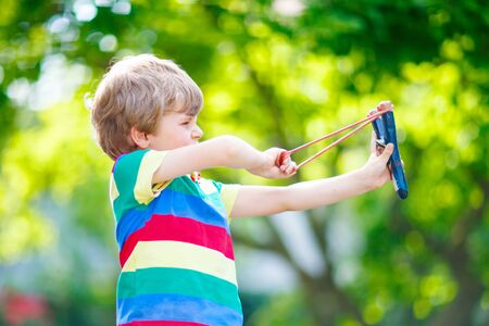 dowdy: little kid boy shooting wooden slingshot
