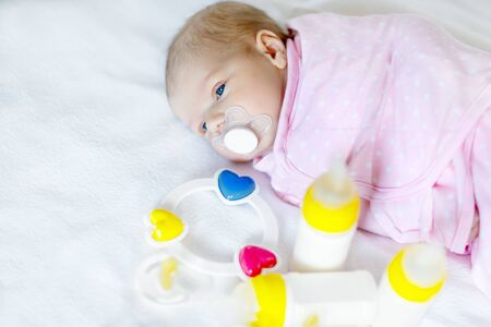 nude little girls: Cute newborn baby girl with nursing bottles and pacifier Stock Photo