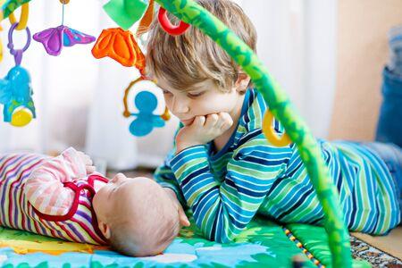 Heureux petit enfant garçon avec bébé nouveau-né soeur fille