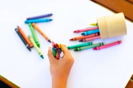 childs hands with lots of colorful wax crayons