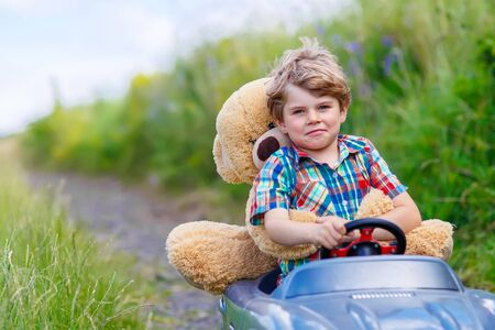Little kid boy driving big toy car with a bear, outdoors. Stock Photo