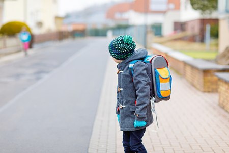 Little kid boy with eye glasses walking from the school Stock Photo