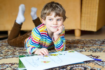 pre teen boy: preschool kid boy at home making homework, painting a story with colorful pens