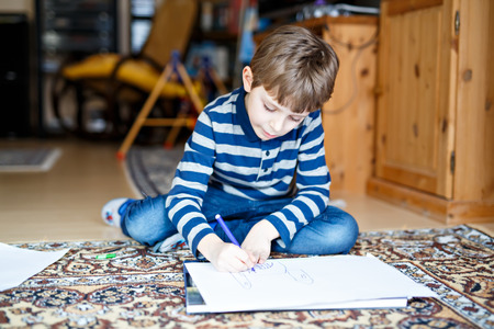 preschool kid boy at home making homework, painting a story with colorful pens