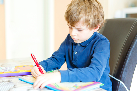 pre teen boy: preschool kid boy at home making homework writing letters with colorful pens
