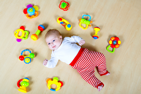 Cute baby girl playing with colorful rattle toys Stockfoto