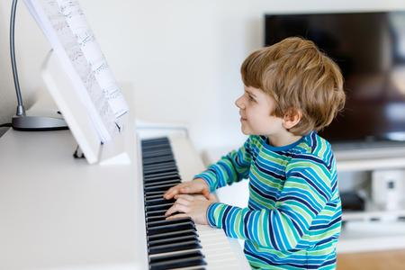 美しい小さな子供男の子リビング ルームや音楽学校でピアノを弾く