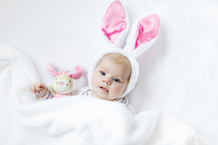 Adorable cute newborn baby girl in Easter bunny costume and ears. Stock Photo - 74179802