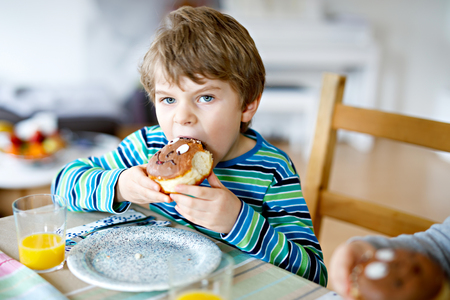 Adorable little preschool boy eating donut indoor Stock Photo