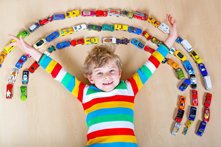 Cute little blond kid boy playing with lots of toy cars indoor.