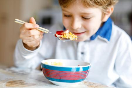작은 금발 학교 아이 소년 우유와 열매, 아침 식사 신선한 딸기와 시리얼을 먹고