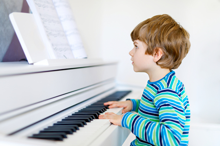 Beautiful little kid boy playing piano in living room or music school