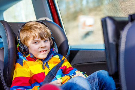 Little blond kid boy watching tv or dvd with headphones during long car drive