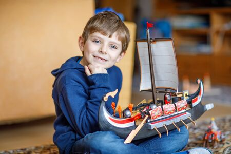 Little blond preschool kid boy playing with toy ship indoors