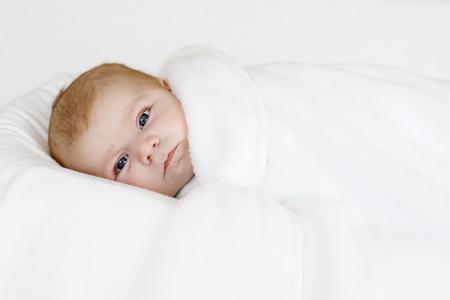 swaddling: Cute little newborn baby girl wrapped in white blanket