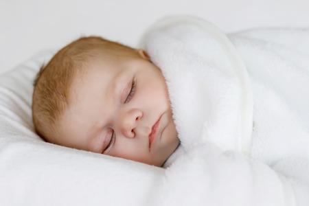 swaddling: Cute little newborn baby girl sleeping wrapped in blanket