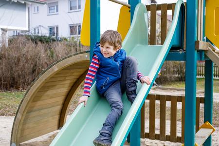 幸せな金髪の子供男の子楽しんで、屋外の遊び場のスライド