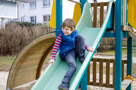 Happy blond kid boy having fun and sliding on outdoor playground Фото со стока