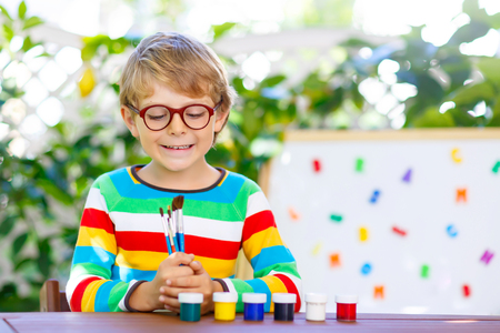 Little kid boy with glasses holding school equipment Stock Photo