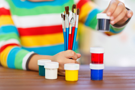 Close-up of hands of kid holding watercolors and brushes. Stock Photo