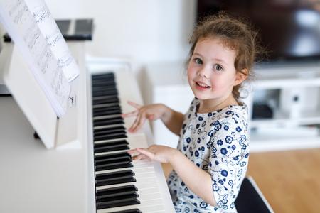 美しい小さな子供女の子リビング ルームや音楽学校でピアノを弾く