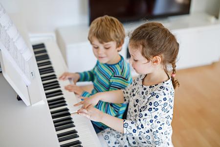 pianista: Dos niños pequeños niña y niño tocando el piano en el salón o escuela de música