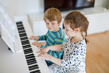 Two little kids girl and boy playing piano in living room or music school