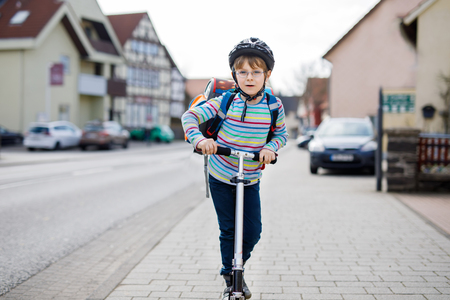 child protection: Little kid boy in helmet riding with his scooter in the city