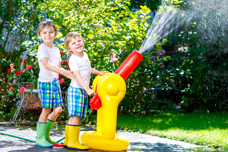 Two little kids boys playing with a garden hose water sprinkler