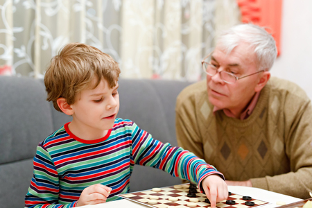 little kid boy and senior grandfather playing together checkers game