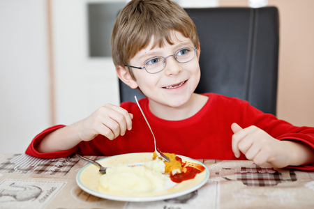 Adorable little school boy eating potato mash and chicken breast indoor Фото со стока