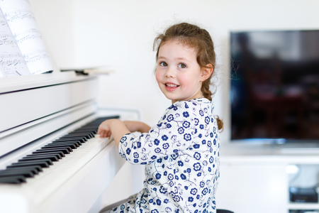 Beautiful little kid girl playing piano in living room or music school