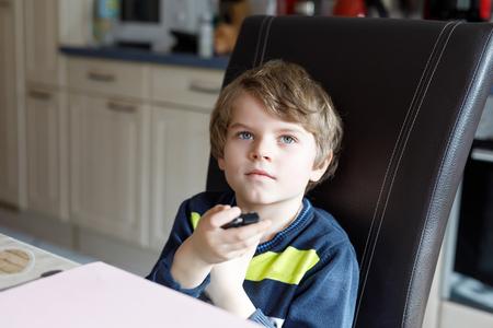 kidsroom: Cute little blond preschool kid boy watching tv.
