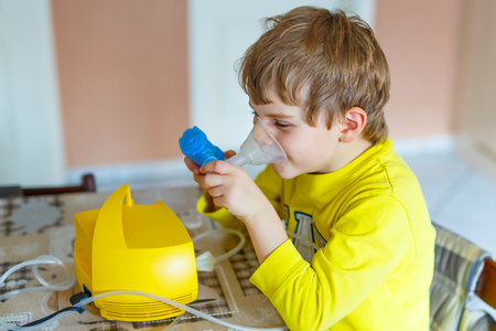 Cute kid boy making inhalation therapy by the mask of inhaler