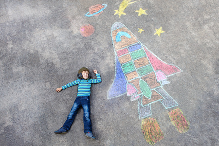 little kid boy flying by a space shuttle chalks picture Stock Photo