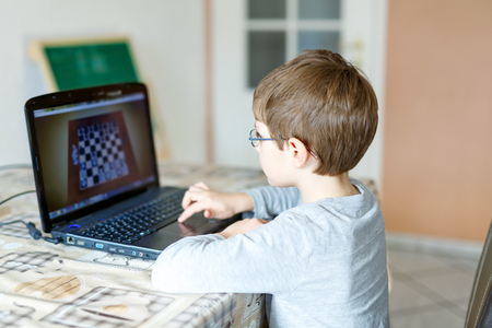 kid boy with glasses playing online chess board game on computer