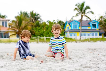 Two kid boys building sand castle on tropical beach